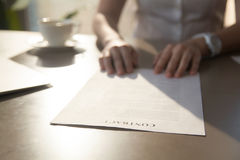 Close up of contract on desk, businesswoman reading contractual. Close up of contract on desk, businesswoman reads contractual terms before making deal while Royalty Free Stock Photo