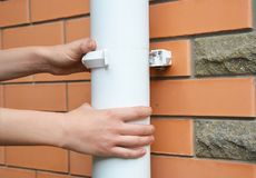 Contractor repair rain gutter downspout pipe. Roundline Guttering, Guttering & Drainage. Close up on Contractor repair rain gutter downspout pipe. Roundline royalty free stock images