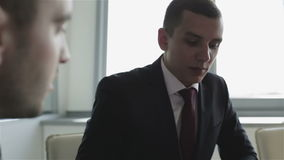 Close-up. Conversation of two businessmen. Suit, tie, serious face. Defocusing one of the objects stock footage