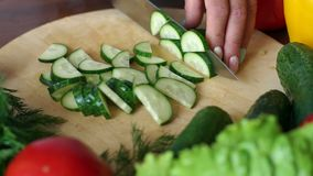 Close-up of cook cutting fresh cucumber on wooden chopping board, slow motion. Cooking vegetable salad at home in the kitchen stock video