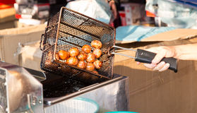 Close up of cook frying meatballs at street market Royalty Free Stock Photos