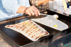Close up of cook frying pancakes at street market Royalty Free Stock Photo