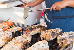 Close up of cook hands grilling fish on street Stock Images