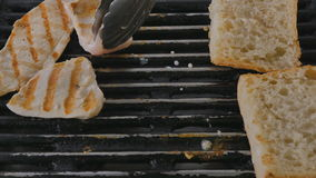 Close-up - the cook preparing a chiken fillet with bread on a grill pan stock footage