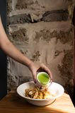 Closeup of cook`s hand pouring green fillet sauce. royalty free stock photo