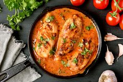 Chicken breast with tomato sauce. Close up of cooked chicken breast with tomato sauce in frying pan. Top view, flat lay Stock Photo