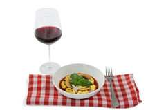 Close up of cooked tortelloni on napkin by wineglass Royalty Free Stock Images