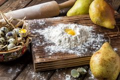 Close up. Cooking autumn pear cake. Making dough from quail eggs and flour on a brown wooden board stock photos