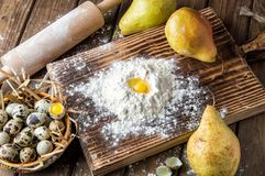 Close up. Cooking Easter cake. Yellow Egg Yolk in a hill of white flour, surrounded by ripe large pears and a bowl of pearl eggs.