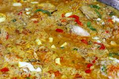 Close up cooking Spanish paella in big frying pan. Close up cooking traditional Spanish Valencian mixed paella with chicken, seafood and vegetables in big frying stock photo