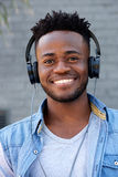 Close up cool young black guy listening to music with headphones. Close up portrait of cool young black guy listening to music with headphones Stock Image