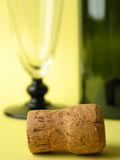 Close-up of a cork. Cork in front of blurry glass and bottle Royalty Free Stock Images