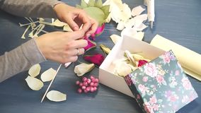 Close-up of corrugated paper hack bright pink in female hands. Female decorator folds of paper origami flower button stock video footage