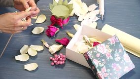 Close-up of corrugated paper hack bright pink in female hands. Female decorator folds of paper origami flower button stock video