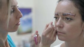 Close-Up Cosmetician Applies Special Remedy with Cotton Bud on Eyebrow of Beautiful Woman Before Tattooing. Close-Up Cosmetician Applies Special Remedy with a stock video footage