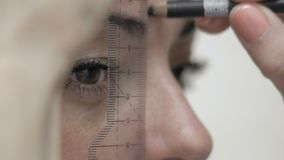 Close-Up Cosmetician Does Eyebrow Marking With Pencil Client For Eyebrow Correction. Close-Up Cosmetician Does Eyebrow Layout Using Rulers and Pencils to Client stock footage