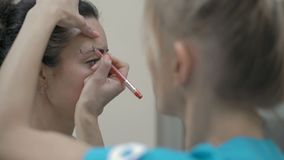 Close-Up Cosmetician Draws Red Borders Around Client Eyebrows for Subsequent Corrections. Close-Up Cosmetician Draws Red Borders Around Client Eyebrows for stock video
