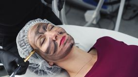 Close up cosmetologist applies black carbon mask to skin of woman face. Beautician preparing client face for laser peeling and treatment stock footage
