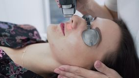 Close-up cosmetologist makes hair laser removal procedure to young woman face at clinic, slow motion
