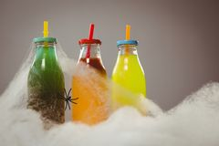 Close up of cotton candy by colorful drinks and spider Stock Photography