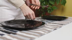 The couple served together table for family dinner, close-up. The couple arranges cutlery and cooked meals on the table. Close-up the couple arranges cutlery and stock footage