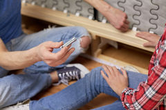 Close up of couple assembling furniture at home Royalty Free Stock Image