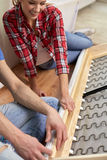 Close up of couple assembling furniture at home Royalty Free Stock Images