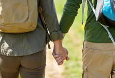 Close up of couple with backpacks holding hands Stock Photos
