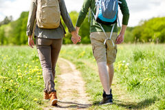 Close up of couple with backpacks walking on road Stock Photo