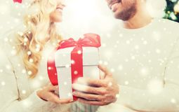 Close up of couple with christmas gift at home. Winter, holidays, christmas and people concept - close up of happy couple with christmas gift at home Royalty Free Stock Image