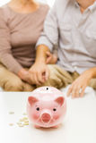 Close up of couple with coins and piggy bank Royalty Free Stock Photos