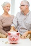 Close up of couple with coins and piggy bank Royalty Free Stock Photography