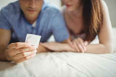 Close-up of couple with a condom on bed. In the bedroom Royalty Free Stock Photos