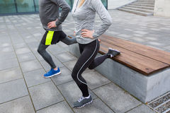 Close up of couple doing lunge exercise on street Stock Photography