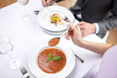 Close up of couple eating appetizers at restaurant. Restaurant, food, people, date and holiday concept - close up of couple eating appetizers at restaurant stock images