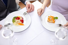 Close up of couple eating appetizers at restaurant. Restaurant, food, people, date and holiday concept - close up of couple eating appetizers at restaurant stock photo
