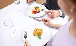 Close up of couple eating appetizers at restaurant. Restaurant, food, people, date and holiday concept - close up of couple eating appetizers at restaurant stock image