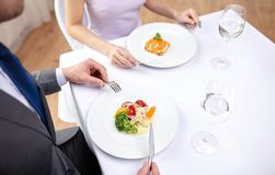 Close up of couple eating appetizers at restaurant. Restaurant, food, people, date and holiday concept - close up of couple eating appetizers at restaurant stock photos