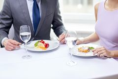 Close up of couple eating appetizers at restaurant. Restaurant, food, people, date and holiday concept - close up of couple eating appetizers at restaurant stock photography