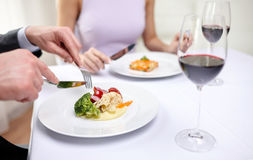 Close up of couple eating appetizers at restaurant. Restaurant, food, people, date and holiday concept - close up of couple eating appetizers at restaurant royalty free stock images