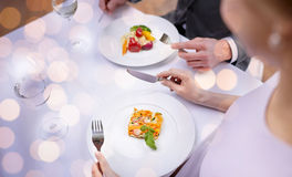 Close up of couple eating appetizers at restaurant. Restaurant, food, people, date and holiday concept - close up of couple eating appetizers at restaurant over stock image