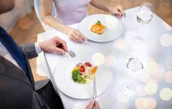 Close up of couple eating appetizers at restaurant. Restaurant, food, people, date and holiday concept - close up of couple eating appetizers at restaurant over royalty free stock photography