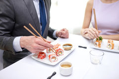 Close up of couple eating sushi at restaurant Royalty Free Stock Images