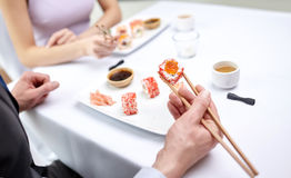 Close up of couple eating sushi at restaurant Stock Photography