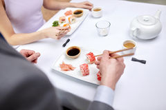 Close up of couple eating sushi at restaurant Stock Image