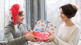 Close up for couple exchanging gifts while celebrating Christmas and New Year together. Man in Santa Claus hat and woman royalty free stock image