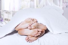 Close-up of couple feet cuddling Royalty Free Stock Photo