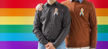 Close up of couple with gay pride rainbow ribbons. Lgbt, same-sex relationships and homosexual concept - close up of male couple with gay pride rainbow awareness Royalty Free Stock Photography