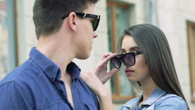 Close up of couple, girl undress sunglasses and looking on boy. Slowly stock video footage