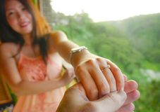 Close up couple hands man holding Asian happy fiance hand with diamond engagement ring on her finger after wedding proposal at royalty free stock photography